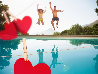 Cheerful couple jumping into swimming pool against hearts hanging on a line